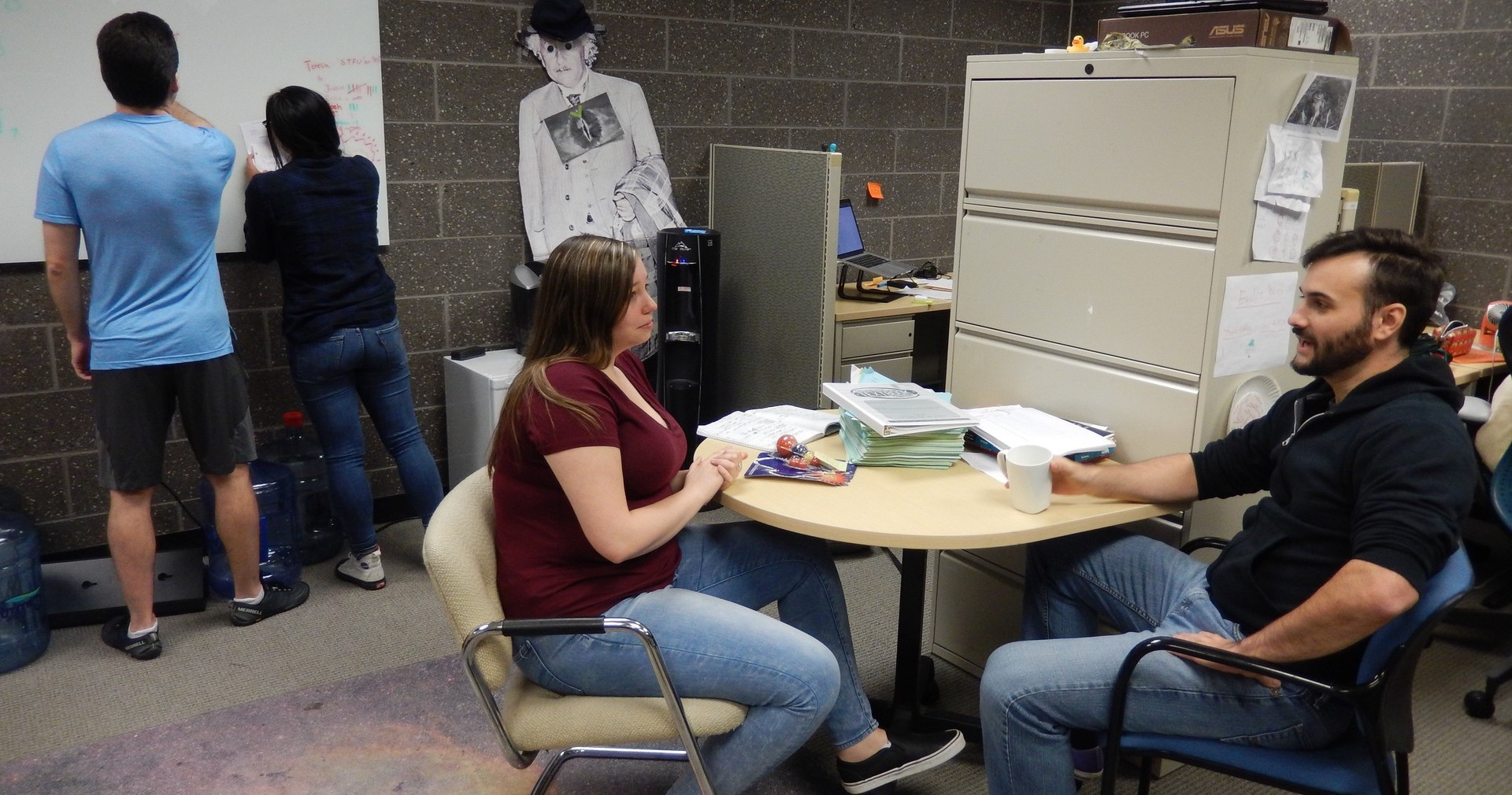 Students confer and work together in the graduate student office